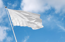 White Blank Flag Waving In The Wind Against Cloudy Sky