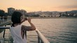 Attractive brunette girl with tattoo takes panorama view of sunset on her smartphone while standing on sea pier in front of city beach