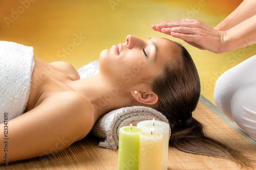 Photo  Woman receiving reiki treatment on forehead.