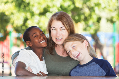 Valokuva  Joyful single parent with sons at park table