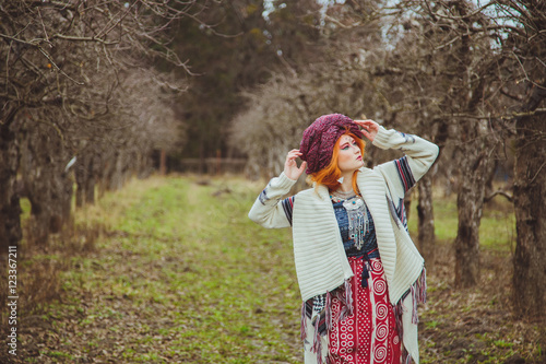 Fotografering  Young girl in extravagant style of ethnic grunge standing in autumn park
