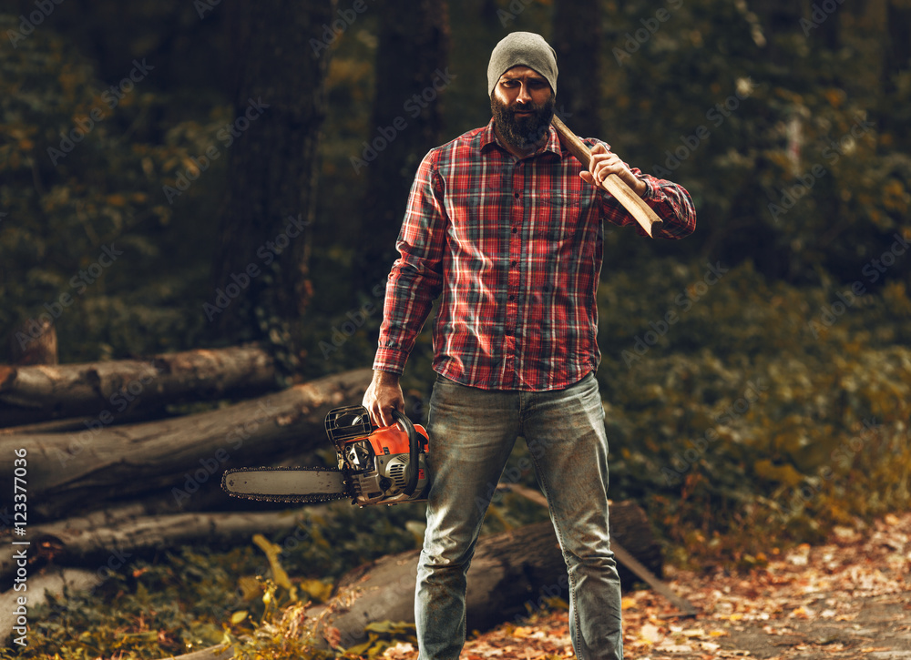 ca2dd32e Fotografiet, Poster Lumberjack worker standing in the forest with axe and  chainsaw på Europosters.se