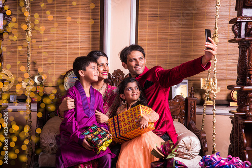 Photo  Asian Indian family taking selfie or self photograph at home with gift boxes on diwali festival