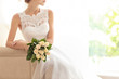 canvas print picture - Bride in beautiful dress with wedding bouquet sitting on sofa