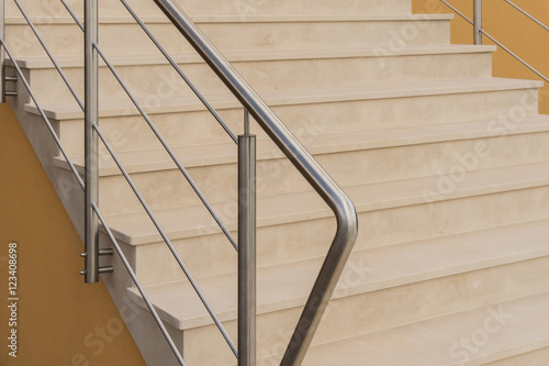 Spoed Foto op Canvas Trappen Moderne Außentreppe aus hellem Naturstein mit Treppengeländer aus Edelstahl - Contemporary outdoor stairs made of light natural stone with railings made of stainless steel in half profile