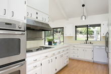 Classic White Kitchen With Wooden Floor And Silver Appliances