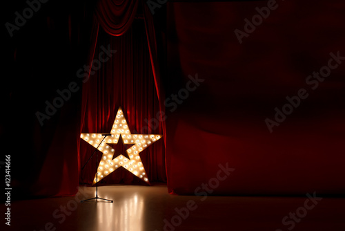 Leinwand Poster Photo of golden star with light bulbs on red velvet curtain on stage
