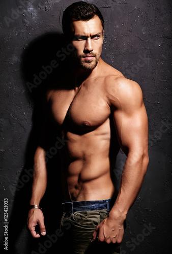 Fotografiet  Portrait of strong healthy handsome Athletic Man Fitness Model posing near dark