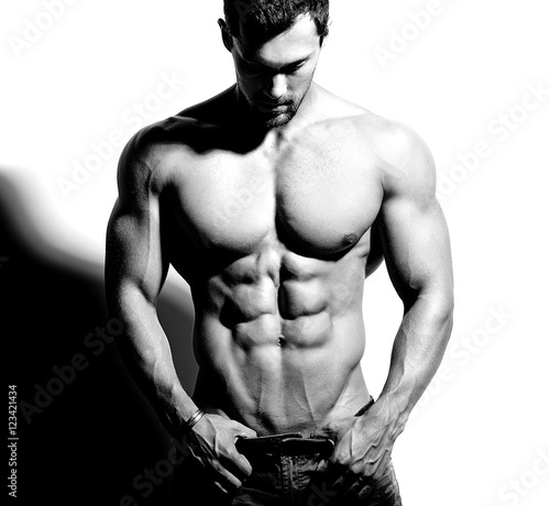 Fotografie, Obraz  Portrait of strong healthy handsome Athletic Man Fitness Model posing near white