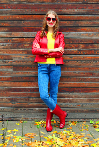 Beautiful woman wearing a red jacket and rubber boots in autumn Fototapete