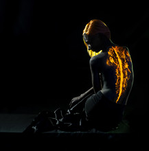 Redhead Girl With Flames Sitting In The Dark
