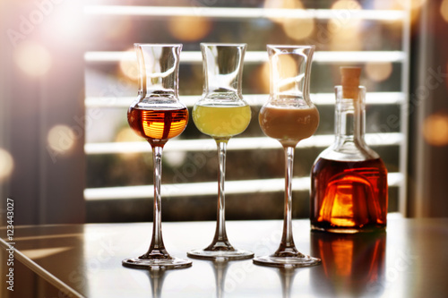 Fotografie, Obraz  Whisky and liqueur in front of a window