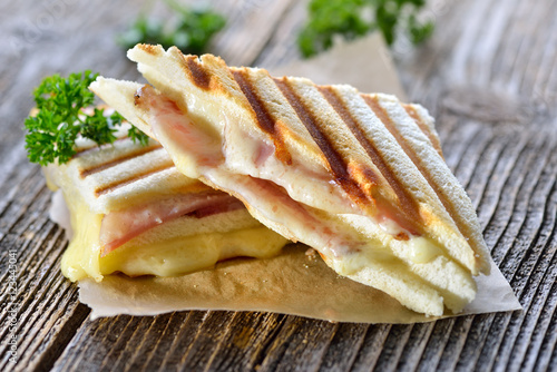 Fotobehang Snack Getoastetes und im Kontaktgrill gepresstes italienisches Panini mit Schinken und Käse - Pressed and toasted double panini with ham and cheese served on sandwich paper on a wooden table