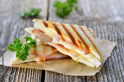Photo Stands Snack Getoastetes und im Kontaktgrill gepresstes italienisches Panini mit Schinken und Käse - Pressed and toasted double panini with ham and cheese served on sandwich paper on a wooden table