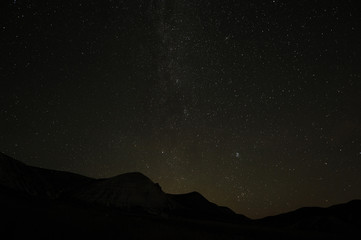 Silhouettes of  mountain peaks and  starry sky.  Milky Way night landscape. Beautiful natural background