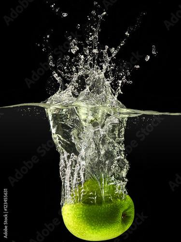 zielony-jablko-spada-w-wodzie-na-czarnym-tle