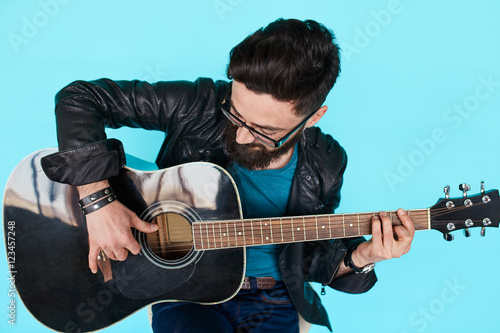 Fotografia, Obraz  Close Bearded hipster man playing on acoustic guitar.