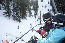 High Angle View Of Girls Reading Map While Riding On Ski Lift