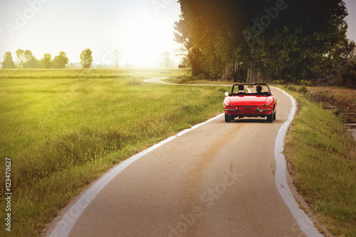 Classic red convertible car traveling in the countryside at sunset