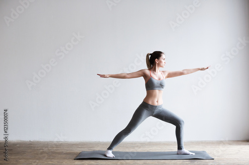 La pose en embrasure Ecole de Yoga Woman doing yoga indoors on yoga mat.