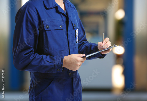 Valokuvatapetti Mechanic in uniform with a clipboard and pen on gas station blurred background
