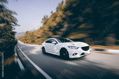 Poster  White car speed driving on asphalt road at daytime