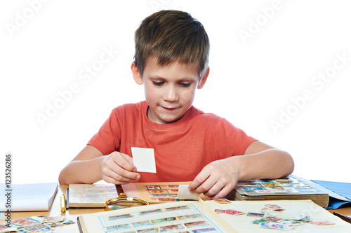 Fotomural  Boy with his collection of old postage stamps isolated