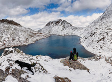 Anonymous Hiker With His Dog Looking Towards Dramatic Snow Covered Mountains And Blue Lake