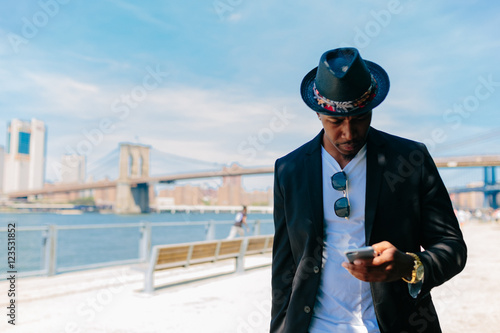 Young Fashionable Businessman Using a Mobile Phone. Manhattan Background New York City