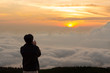 Young man traveler taking photo with smartphone at mountains in morning Lifestyle concept, copy space