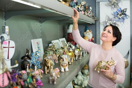 Stampe  Mature woman near souvenirs shelves