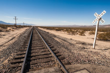 Railroad Crossing Sign By Railway Tracks In The Mojave Desert,southern California