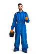 Smiling young mechanic in boiler suit giving thumb up against