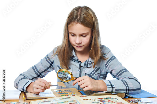 Foto  Teen girl with magnifier looks his stamp collection isolated