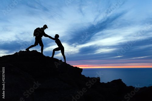 Photo Teamwork couple hikers silhouette in mountains, climbers team