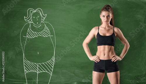 Fotografie, Obraz  Sporty girl with slim body and drawing of woman on chalkboard