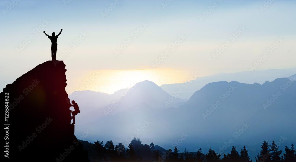 Fototapeta Bergsteiger auf einem Gipfel im Gebirge bei Sonnenaufgang