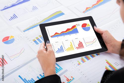 Businesswoman Analyzing Financial Graphs Using Digital Tablet