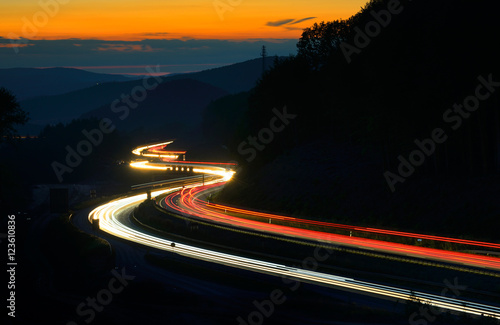 Papiers peints Autoroute nuit Winding Motorway through Hill Landscape at night, long exposure of headlights and taillights in blurred motion