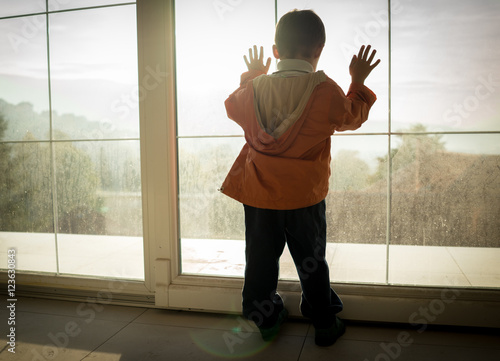 Fotografia, Obraz  A little boy looking trough the window