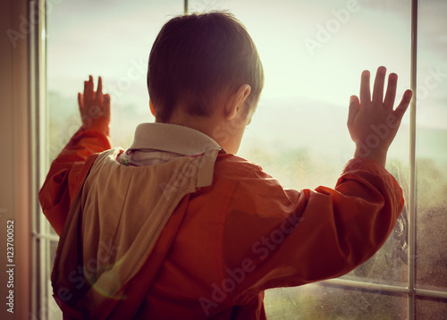 Fotografering  A little boy looking trough the window