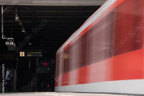 Foto auf AluDibond Bahnhof vorbeifahrender roter Zug am Bahnsteig