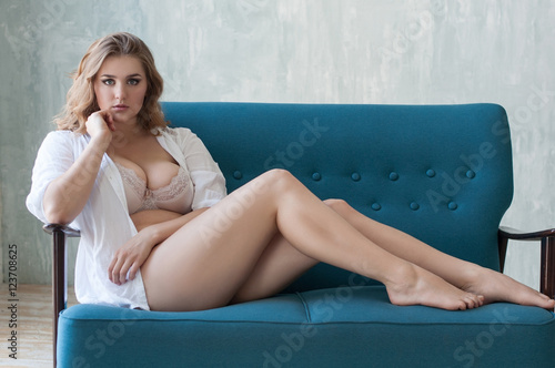 Carta da parati beautiful chubby girl in underwear and a shirt sitting on a sofa