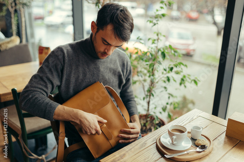 Fototapety, obrazy: Handsome businessman with leather bag sitting at the table