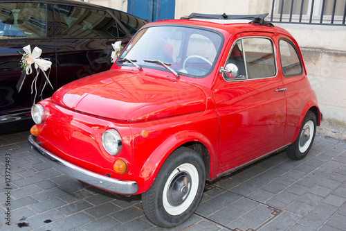 Deurstickers Oude auto s Red small retro car at the city street