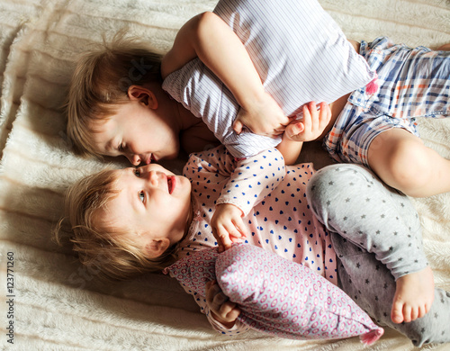 Two little kids lies on the bed and touching. Wallpaper Mural