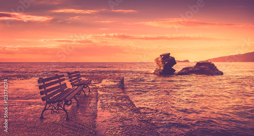 Foto op Plexiglas Crimson Sunrise scene at the sea. There are two benches and two cliffs into the water.