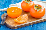 Cut persimmon fruits on wooden board and table, horizontal