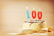 Leinwanddruck Bild - Birthday cake with burning candle as a number one hundred. Focus on the candle