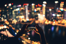 Silhouette Of Woman Using Smartphone For Taking Pictures Of City Skyline At Night